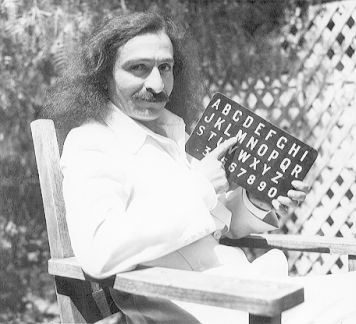Meher Baba sitting in a garden in Hollywood in 1932 points to a letter on his alphabet board